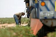 Miguel Holguin, an oil field worker who immigrated from Mexico, prepares a swabbing rig in a field in Seminole