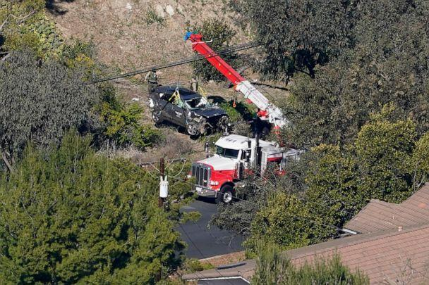 PHOTO: Workers move a vehicle after a rollover accident involving golfer Tiger Woods, Feb. 23, 2021, in the Rancho Palos Verdes section of Los Angeles. (Mark J. Terrill/AP)