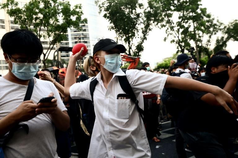 A pro-democracy protester prepares to throw a water balloon at the court