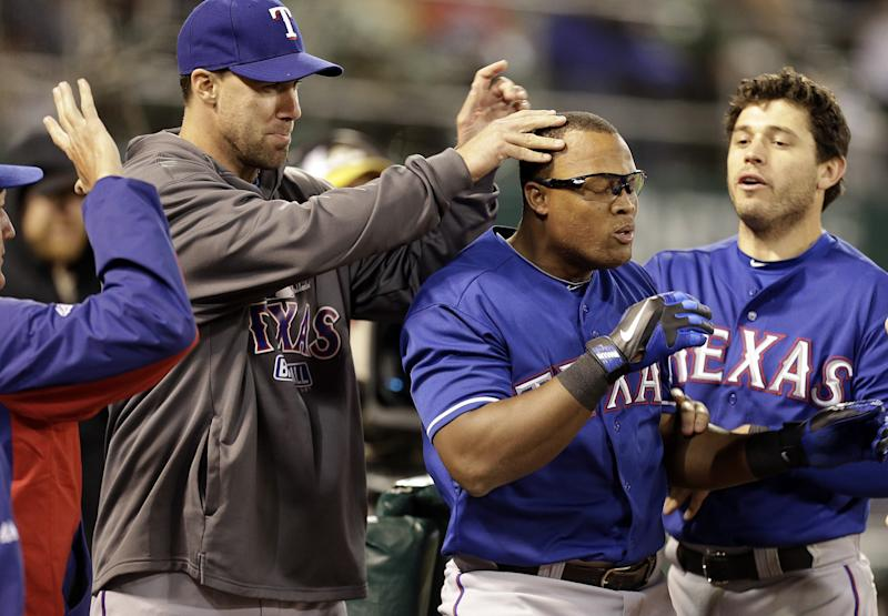 In this May 14, 2013 file photoTexas Rangers' Adrian Beltre, center, is congratulated by teammates after hitting a home run off Oakland Athletics' Chris Resop in the tenth inning of a baseball game Tuesday, May 14, 2013, in Oakland, Calif. The Gold Glove third baseman plays without wearing a protective cup. And he really hates being touched on the head _ a fact that gets mercilessly exploited by his Texas Rangers teammates, especially when he keeps hitting home runs.
