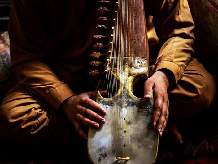 A stock image of a man playing the rubab
