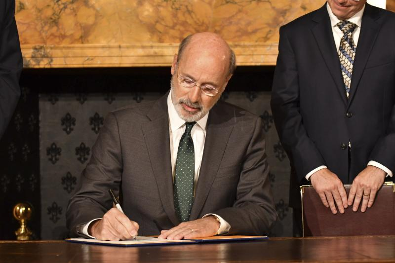 Pennsylvania Gov. Tom Wolf signs an executive order for his administration to start working on regulations to bring Pennsylvania into a nine-state consortium that sets a price and limits on greenhouse gas emissions from power plants, Thursday, Oct. 3, 2019 in Harrisburg, Pa. The move is part of Wolf's effort to fight climate change in the nation's fourth-biggest emitter of greenhouse gases. (AP Photo/Marc Levy)