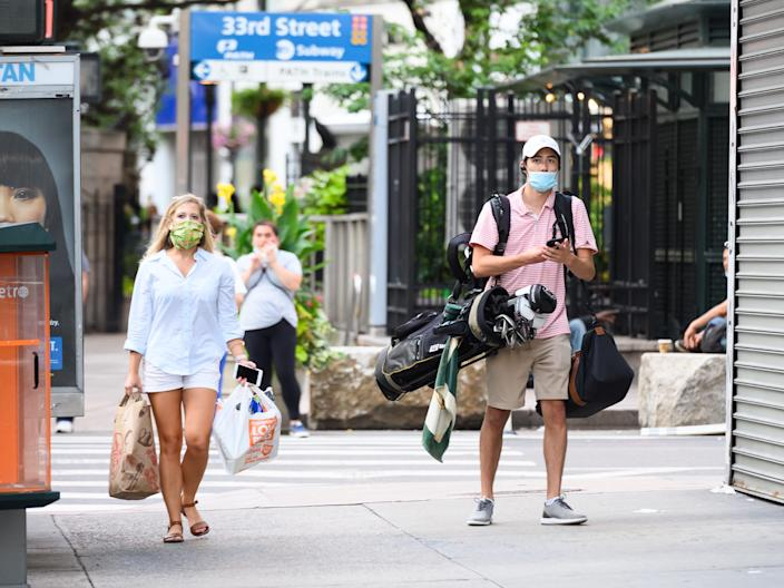 A person wears a protective face mask and carries golf clubs in midtown as New York City moves into Phase 3 of re-opening following restrictions imposed to curb the coronavirus pandemic on July 12, 2020.