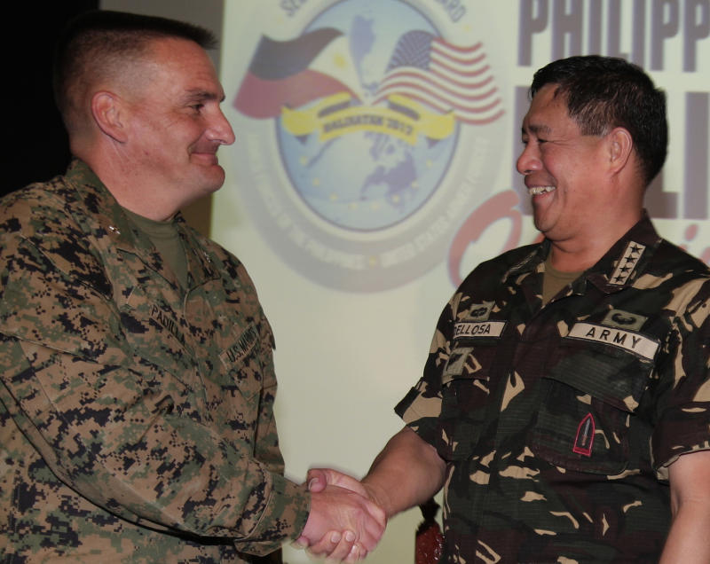 U.S. Balikatan 2012 Exercise Director, U.S. Marine Corp. Brig. Gen. Frederick Padilla, left, shakes hands with Philippine military chief Gen. Jesse Dellosa during the opening of an annual military drill called Balikatan or shoulder-to-shoulder at Camp Aguinaldo, military  headquarters in suburban Quezon City, north of Manila, Philippines on Monday April 16, 2012. U.S. and Philippine military officials say nearly 7,000 American and Filipino troops have begun two weeks of major military exercises but they stress that China is not an imaginary target. (AP Photo/Aaron Favila)