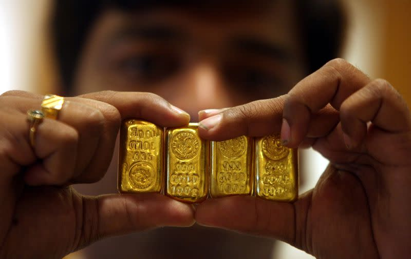 Gold dips on profit-taking, but eyes weekly gain on economic woes