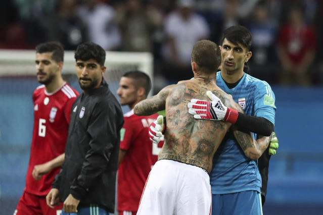 Spain's Sergio Ramos, center, embraces Iran goalkeeper Ali Beiranvand at the end of the group B match between Iran and Spain at the 2018 soccer World Cup in the Kazan Arena in Kazan, Russia, Wednesday, June 20, 2018. (AP Photo/Thanassis Stavrakis)