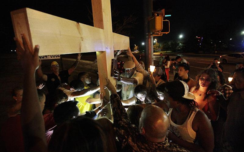 People place hands on a large wooden cross as they pray late Saturday, July 21, 2012, across the street from the movie theater in Aurora, Colo. where a gunman killed at least 12 people and wounded dozens of others Friday in one of the deadliest mass shootings in recent U.S. history. (AP Photo/Ted S. Warren)