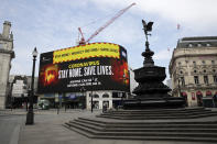 FILE - In this Wednesday, April 8, 2020 file photo a video screen displays a message urging people to stay home in a nearly deserted Piccadilly Circus in London. More than 100,000 people have died in the United Kingdom after contracting the coronavirus. That's according to government figures released Tuesday Jan. 26, 2021. (AP Photo/Matt Dunham, File)