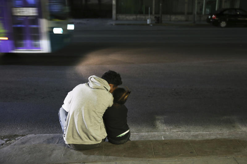 In this July 18, 2019 photo, a migrant father and daughter sit on the sidewalk after getting off a bus that brought them all the way from Nuevo Laredo to Monterrey, Mexico, Thursday, July 18, 2019. The group was placed on the bus by Mexican migration authorities, arriving in this northern Mexican city late at night and left them to fend for themselves with no support on housing, work or schooling for children, who appear to make up about half the group. (AP Photo/Marco Ugarte)