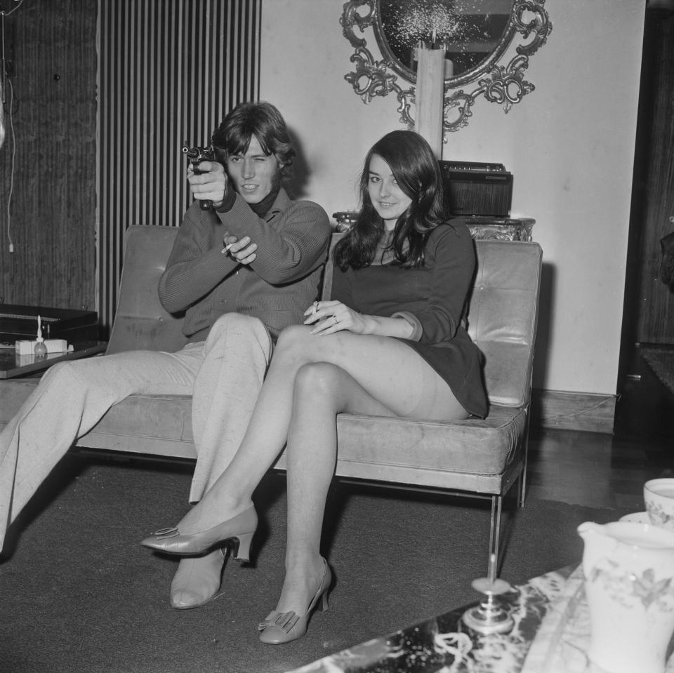 British singer and songwriter Barry Gibb pointing a gun, while sitting next to his girlfriend, former Miss Edinburgh Linda Gray, UK, 19th October 1968. (Photo by Pierre Manevy/Daily Express/Getty Images)