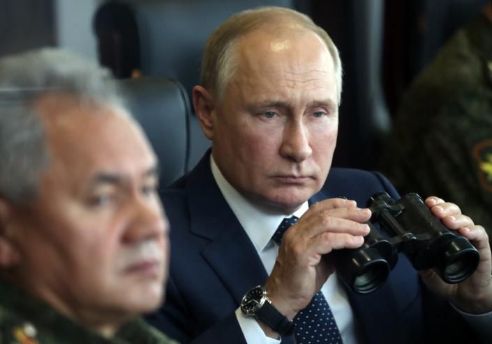 Russian President Vladimir Putin, right, holds a binoculars as Russian Defense Minister Sergei Shoigu sits near watching the joint strategic exercise of the armed forces of the Russian Federation and the Republic of Belarus Zapad-2021 at the Mulino training ground in the Nizhny Novgorod region, Russia, Monday, Sept. 13, 2021. The military drills attend by servicemen of military units and divisions of the Western Military District, representatives of the leadership headquarters and personnel of military contingents of the armed forces of Armenia, Belarus, India, Kazakhstan, Kyrgyzstan and Mongolia. (Sergei Savostyanov, Sputnik, Kremlin Pool Photo via AP)
