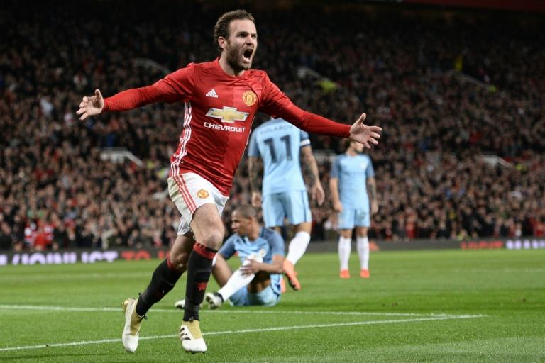 Manchester United's Spanish midfielder Juan Mata celebrates after scoring the opening goal against Manchester City on October 26, 2016