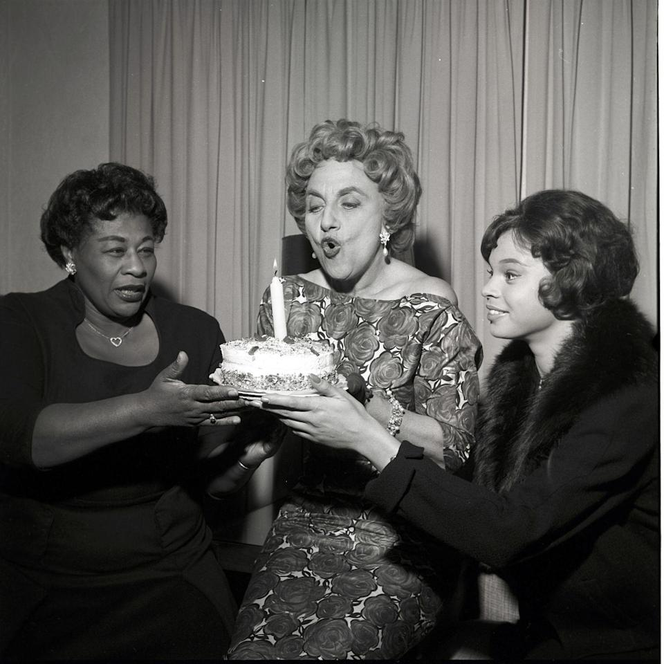 <p>Juliet Prowse and Ella Fitzgerald present their costar, Hermione Gingold, with a birthday cake. The three stars were appearing on <em>The Frank Sinatra Show</em> together. </p>