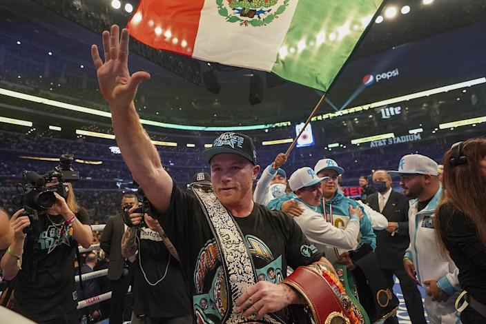 Canelo Álvarez carries his title belts in the ring as others take photos and mill around smiling