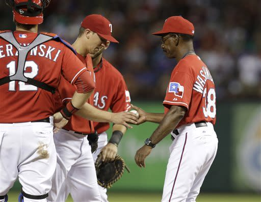 Texas Rangers manager Ron Washington (38) pulls starting pitcher Ross Wolf, center, as catcher A.J. Pierzynski (12) watches during the third inning of a baseball game against the Baltimore Orioles on Saturday, July 20, 2013, in Arlington, Texas. (AP Photo/LM Otero)