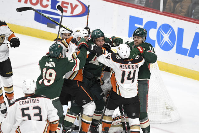 Minnesota Wild's Jordan Greenway, center, is surrounded by Wild teammates and Anaheim Duck players after getting off a shot on the Ducks' goal in the first period of an NHL hockey game, Tuesday, Dec. 10, 2019, in St. Paul, Minn. (AP Photo/Tom Olmscheid)