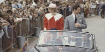 <p>While driving through Memorial Oval in Port Pirie, Diana wears a Jan Van Velden suit and a hat by John Boyd. Charles smiles at the crowd in a grey suit. </p>