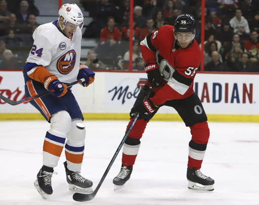 New York Islanders defenceman Scott Mayfield (24) blocks a shot as Ottawa Senators left wing Magnus Paajarvi (56) looks on during first-period NHL hockey game action in Ottawa, Ontario, Thursday, March 7, 2019. (Fred Chartrand/The Canadian Press via AP)