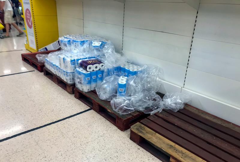 Depleted stocks and empty pallets in the toilet roll aisle at the Portsmouth North Harbour Tesco (PA)