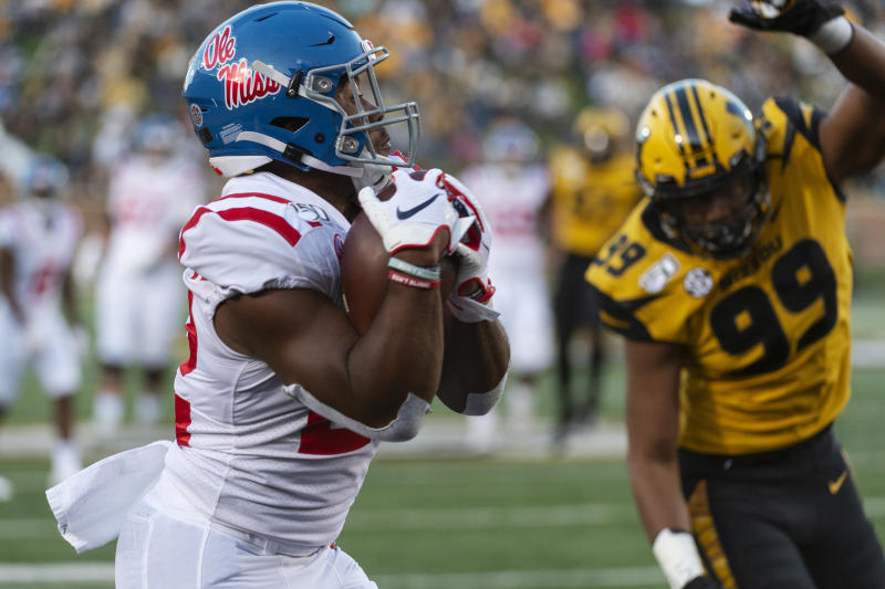 Mississippi running back Scottie Phillips, left, catches a touchdown pass in front of Missouri defensive lineman Isaiah McGuire, right, during the first quarter of an NCAA college football game Saturday, Oct. 12, 2019, in Columbia, Mo. (AP Photo/L.G. Patterson)