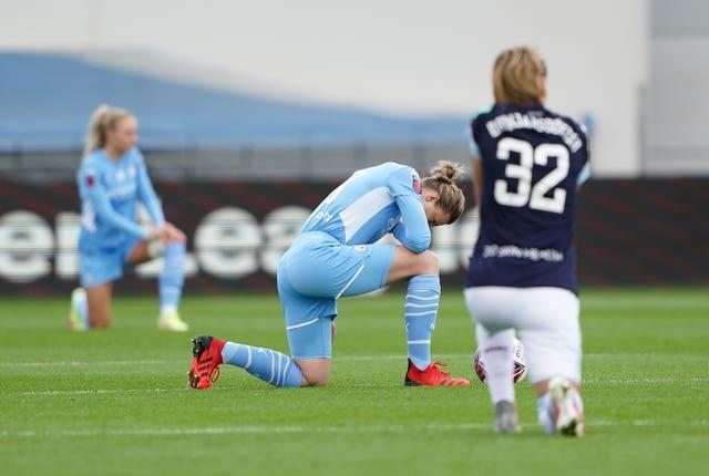 City's Ellen White (centre) taking a knee prior to the match against West Ham earlier this month (Zac Goodwin/PA).