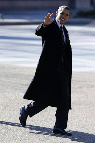 President Barack Obama waves to reporters shouting questions at him regarding the fiscal cliff as he crosses Pennsylvania Ave in front of the White House in Washington, Thursday, Dec. 13, 2012, as he goes to a holiday party at Blair House. (AP Photo/Charles Dharapak)