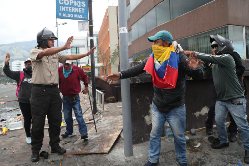 Anti-government protesters abandon their position near the National Assembly after security forces launched tear gas to disperse them, in Quito, Ecuador, Friday, Oct. 11, 2019. Hundreds more indigenous protesters poured into Ecuador's capital from the country's Amazon on Friday, increasing pressure on President Lenín Moreno amid protests against fuel price hikes that have produced dramatic images of paraded police captives and violent clashes. (AP Photo/Fernando Vergara)