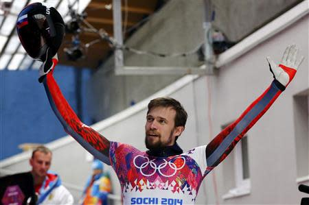 Russia's Alexander Tretiakov waves to the crowd after competing in the men's skeleton event at the 2014 Sochi Winter Olympics February 14, 2014. REUTERS/Arnd Wiegmann