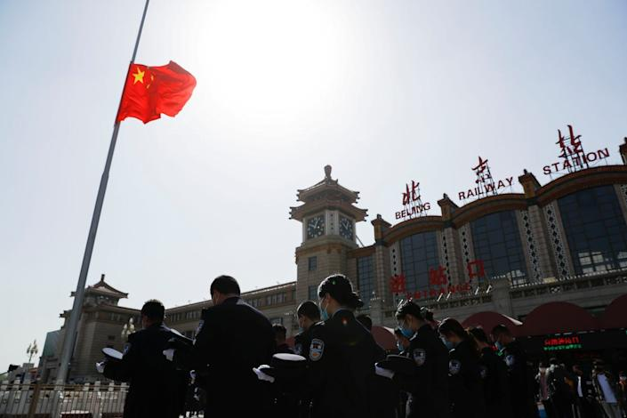 Security personnel outside Beijing Railway Station took off their caps and bowed their heads during the national moment of silence.