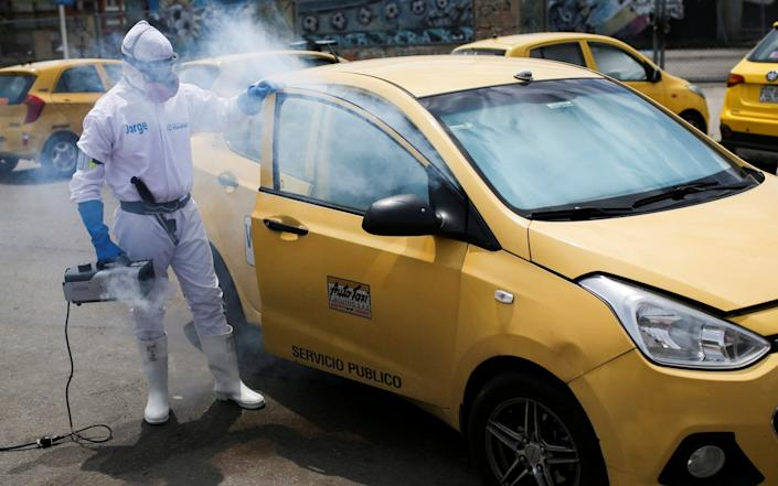 A worker disinfects the interior of a taxi amidst an outbreak of Covid-19 in Bogota, Colombia - Reuters