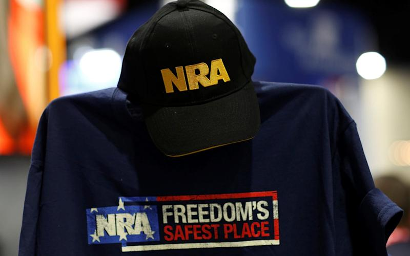 A cap and shirt are displayed at the booth for the National Rifle Association (NRA) at the Conservative Political Action Conference (CPAC) at National Harbor, Maryland - REUTERS