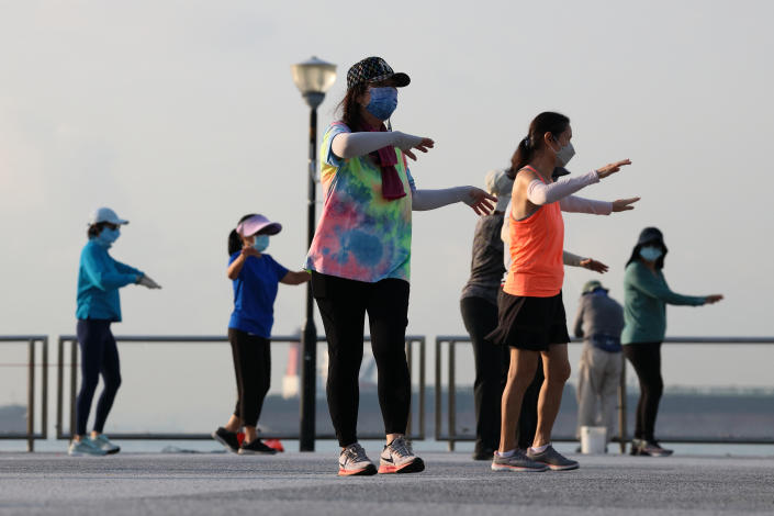People wearing protective mask exercise at a park on September 20, 2021 in Singapore.  (Photo by Suhaimi Abdullah/NurPhoto via Getty Images)