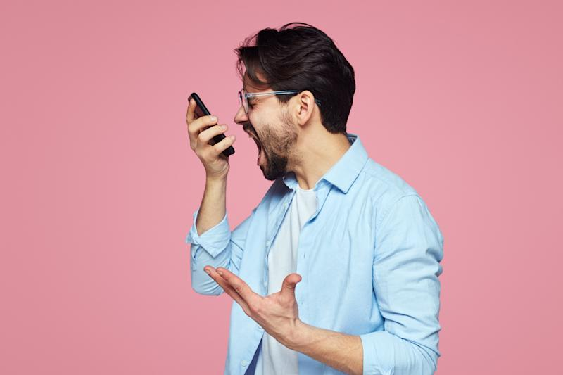Image of aggressive young man in blue shirt screaming at smartphone while having mobile conversation isolated over pink background