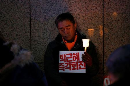 """A man attends a protest calling for South Korean President Park Geun-hye to step down in central Seoul, South Korea, November 29, 2016. The sign reads """"Step down Park Geun-hye immediately"""". REUTERS/Kim Hong-Ji"""