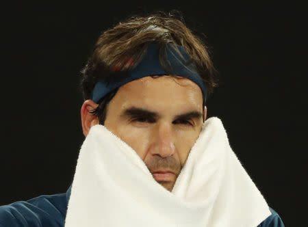 Tennis - Australian Open - Fourth Round - Melbourne Park, Melbourne, Australia, January 20, 2019. Switzerland's Roger Federer wipes his face with a towel during the match against Greece's Stefanos Tsitsipas. REUTERS/Adnan Abidi