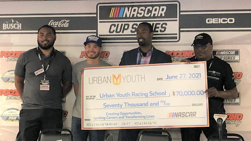 <em>Gerald Taylor of NASCAR, Hendrick Motorsports driver Kyle Larson, NASCAR VP of diversity and inclusion Brandon Thompson, and Urban Youth Racing School founder Anthony Martin announce a donation of $70,000 to the UYRS Sunday at Pocono. Photo Credit: Chris Estrada</em>