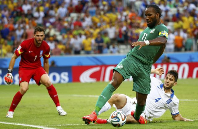 Ivory Coast's Drogba is challenged for the ball by Greece's Manolas in front of Greece's Karnezis during their 2014 World Cup Group C soccer match at the Castelao arena in Fortaleza