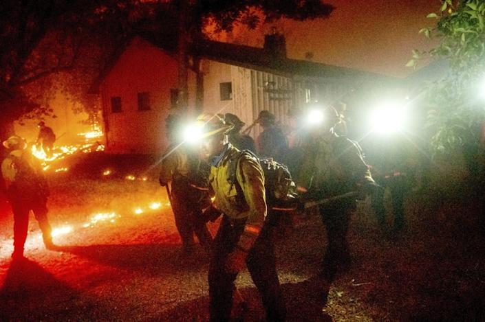 "A hand crew works to save a home as the Bear fire burns through the Berry Creek area of Butte County on Wednesday. <span class=""copyright"">(Noah Berger / Associated Press)</span>"