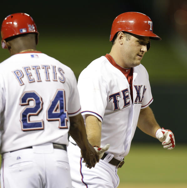Texas Rangers designated hitter Lance Berkman, right, gets a congrats from third base coach Gary Pettis, left, as he rounds the bases after hitting a two-run homer in the seventh inning of a baseball game against the Cleveland Indians Monday, June 10, 2013, in Arlington, Texas. Texas Elvis Andrus scored on the play and the Rangers won 6-3. (AP Photo/LM Otero)