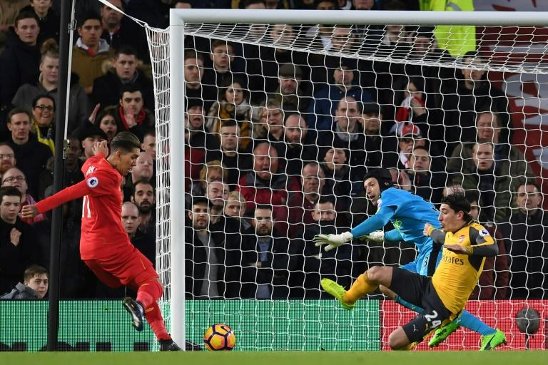 Liverpool's midfielder Roberto Firmino (L) prepares to shoot past Arsenal's goalkeeper Petr Cech to score the opening goal of the English Premier League football match March 4, 2017