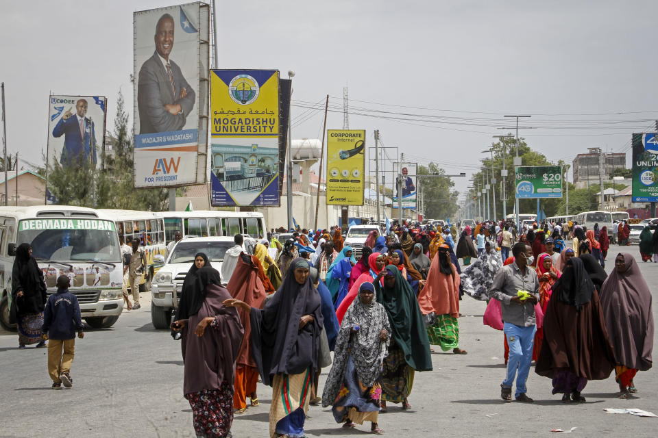 Somalis walk past billboards showing candidates Abdirahman Abdishakur Warsame and Omar Abdulkadir Ahmedfiqi in Mogadishu, Somalia Friday, Jan. 29, 2021. As Somalia marks three decades since a dictator fell and chaos engulfed the country, the government is set to hold a troubled national election but two regional states are refusing to take part in the vote to elect Somalia's president and time is running out before the Feb. 8 date on which mandates expire. (AP Photo/Farah Abdi Warsameh)