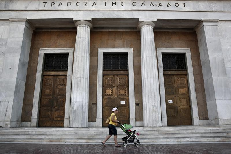 A woman pushes a baby cart in front of the Bank of Greece in Athens