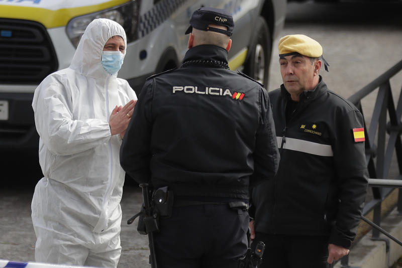 A member of UME, left, talks with a police officer at a ice-skating rink in Madrid, Spain, Tuesday, March 24, 2020. Madrid's ice-skating rink is now being used as a makeshift morgue given the rapid increase in deaths in the Spanish capital owing to the Covid-19 outbreak. For most people, the new coronavirus causes only mild or moderate symptoms. For some, it can cause more severe illness, especially in older adults and people with existing health problems. (AP Photo/Manu Fernandez)