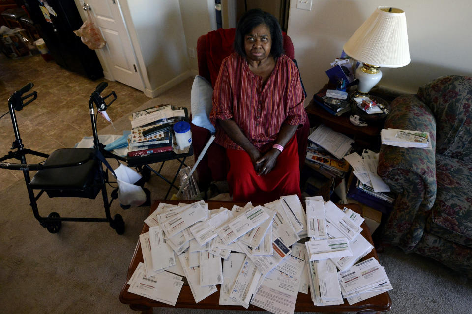 Debra Smith, 57, sits with her medical bills in her living room on Thursday, Oct. 7, 2021, in Spring Hill, Tenn. Smith, who has health problems that prevent her from working, has about $10,000 in unpaid medical bills. Patient advocates and some state governments say hospitals must do more to help patients deal with medical bills before the debt winds up in collections. (AP Photo/Mark Zaleski)