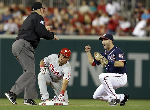 Washington Nationals second baseman Stephen Lombardozzi, right, celebrates as umpire Jeff Nelson (45) calls Philadelphia Phillies' Freddy Galvis, center, out at second as he tried to reach second on his hit during the fifth inning of a baseball game at Nationals Park, Friday, Sept. 13, 2013, in Washington. (AP Photo/Alex Brandon)