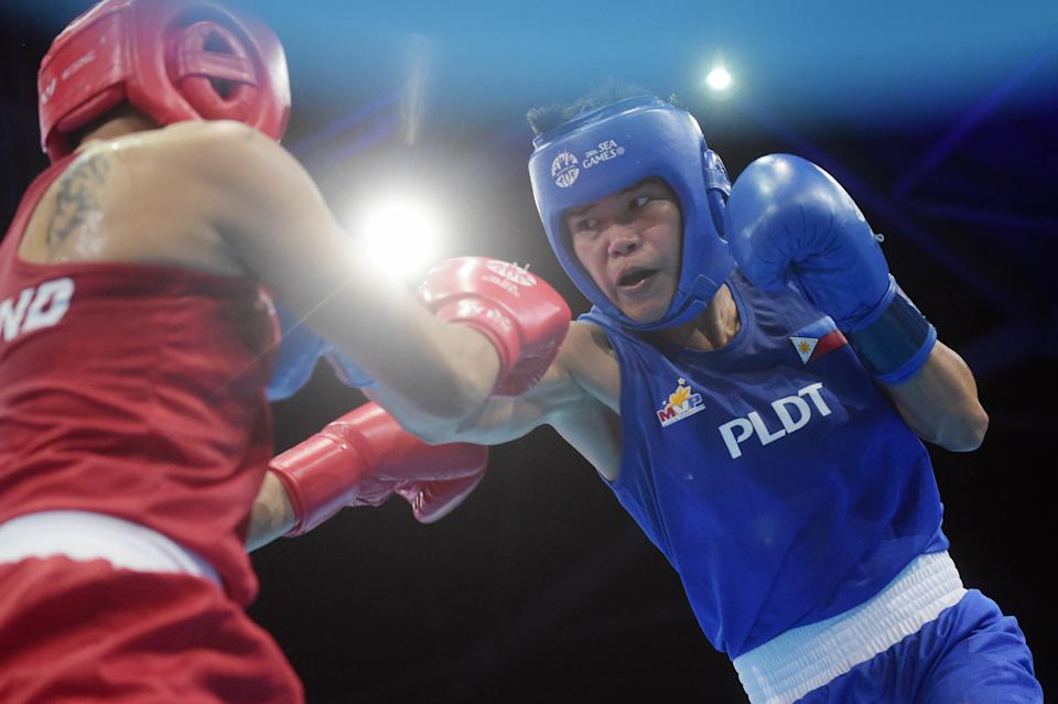 Irish Magno of the Philippines, left, hits Sopida Satumrum of Thailand in a Women's Flyweight (51kg) Semifinal bout at the SEA Games in Singapore, Monday, June 8, 2015.(AP Photo/Joseph Nair)
