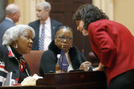 State Sens. Louise Lucas, D-Portsmouth, left, Mamie Locke, D-Hampton, center, and Barbara Favola, D-Arlington, right, confer before a number of gun-related bills were debated in the Senate, Thursday, Jan. 16, 2020, at the Capitol in Richmond, Va. (Bob Brown/Richmond Times-Dispatch via AP)