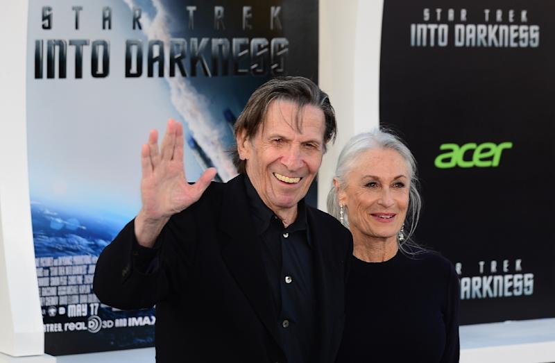 """Leonard Nimoy, who played the role of 'Spock' in the Star Trek TV and film franchise, gives the famous 'Vulcan' greeting next to his wife at the Los Angeles premiere of the movie 'Star Trek Into Darkness"""" in Hollywood, California on May 14, 2013 (AFP Photo/Frederic J. Brown)"""