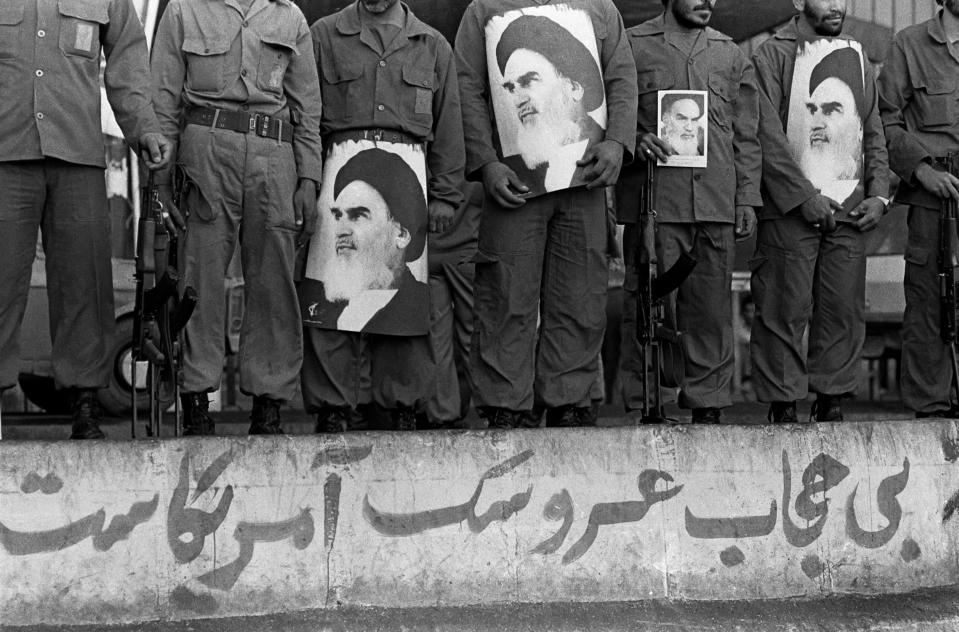 Revolutionary Guard Corps assemble while holding AK-47 automatic assault rifles and pictures of Islamic Republic's leader Ayatollah Khomeini, on Pasdarans Day, commemorating their foundation, in Tehran, Iran, 6th June 1981. (Photo: Kaveh Kazemi/Getty Images)