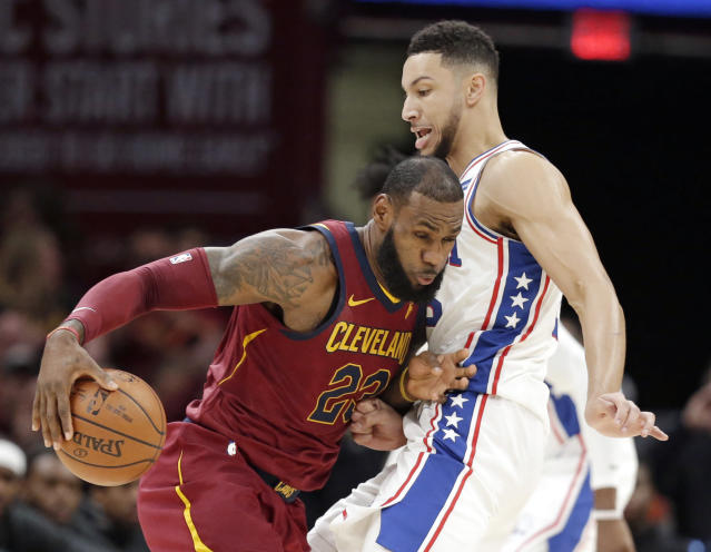 Cleveland Cavaliers' LeBron James, left, drives past Philadelphia 76ers' Ben Simmons during the first half of an NBA basketball game, Saturday, Dec. 9, 2017, in Cleveland. (AP Photo/Tony Dejak)